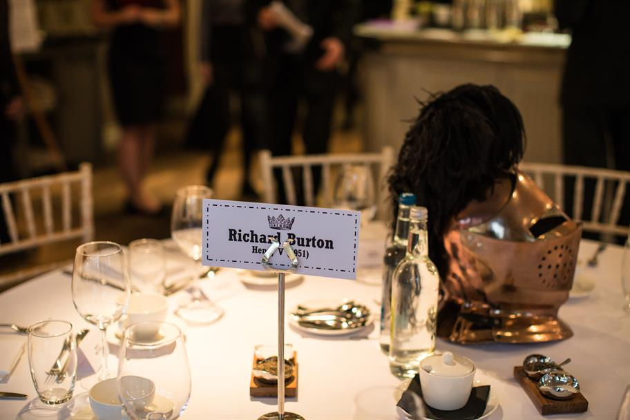 A name tag on a round dinner table reading: Richard Burton, Henry V, next to a polished bronze helmet with black tassel