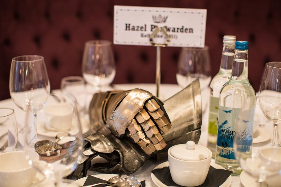 A name tag reading: Hazel Penwarden, next to a pair of polished gauntlets on a dinner table