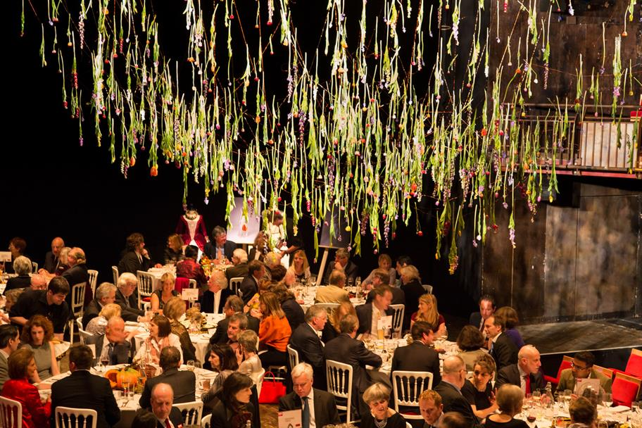 Dinner tables full of guests at the artistic directors' dinner, with a vast floral decoration hanging above their heads