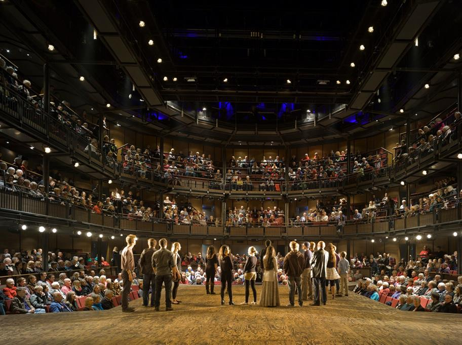 A group of people on the Royal Shakespeare Theatre stage facing a full house of audience