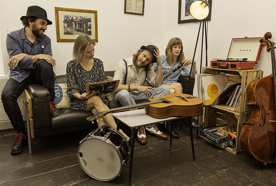 Group of musicians sitting on a sofa surrounded by instruments