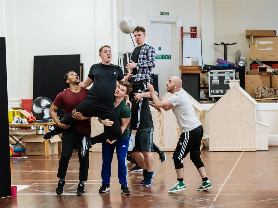 Members of the acting company rehearse a scene from The Boy in the Dress. An actor is held up by 2 others as he headers a ball on a stick.