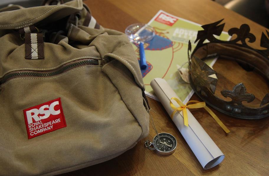 An RSC Adventure bag with compass, scroll, crown and magnifying glass.