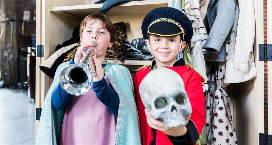 Two children dressing up, one in a cloak playing a trumpet, one in military uniform holding a skull