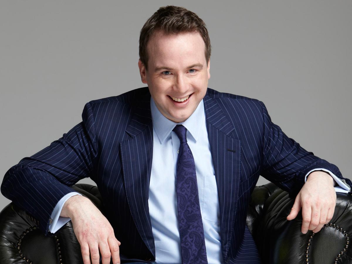 Matt Forde seated in a black leather armchair