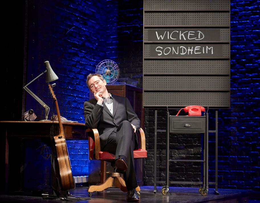 A man in a suit sits in a chair next to a blackboard, a small table with a red telephone, and a guitar.