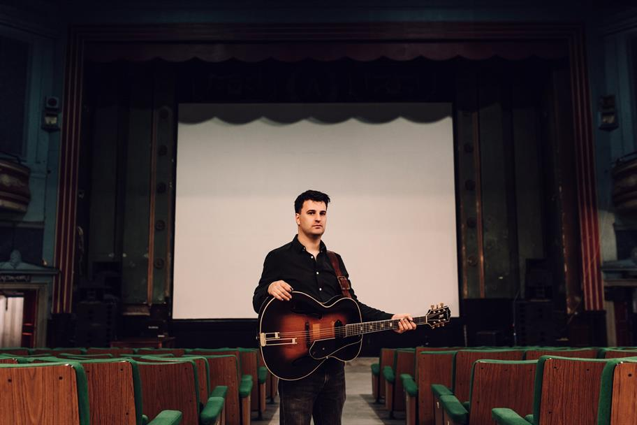 Jim Moray stands with his guitar in a theatre auditorium