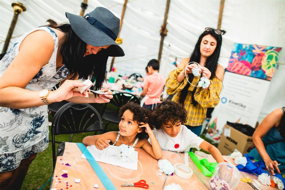 families make floral headbands together for a midsummer party