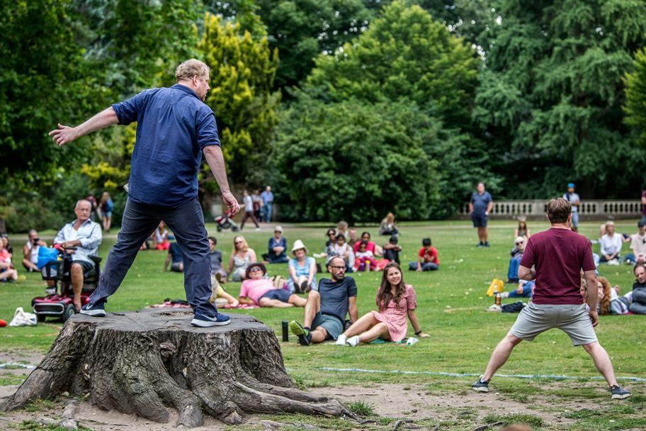 man standing on a tree stump performing outdoors to small groups of people