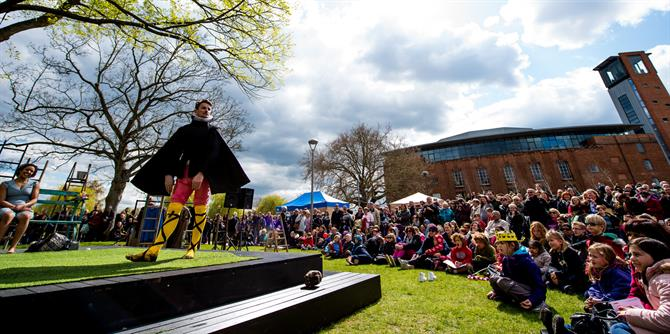 An actor wearing a black cape and yellow cross garters strut around on the outdoor stage, surrounded by a big audience