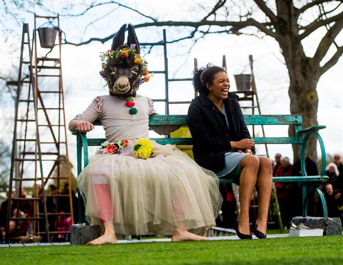 Bottom with a donkey's head and a flowery dress sits on a bench next to a laughing actor