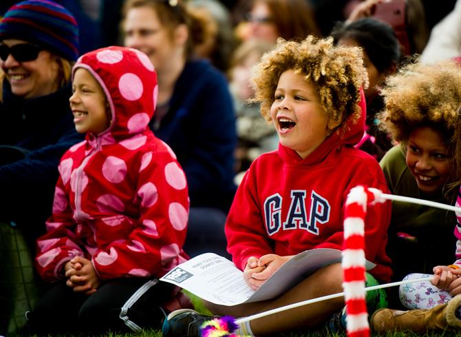 Two children in red coats sitting among a crowd, smiling and laughing