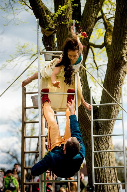 Romeo and Juliet hanging on a ladder, holding their hands out to each other