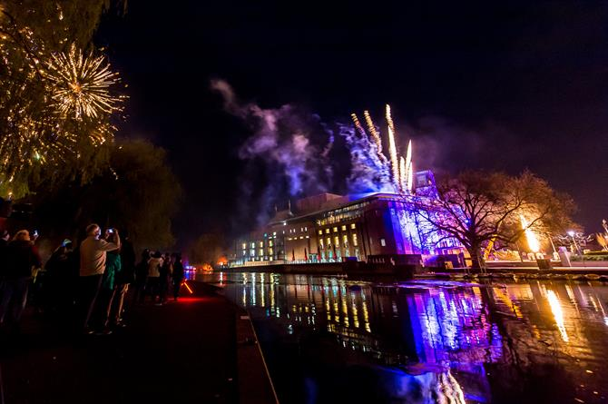 Gold and blue fireworks come out of the RSC building and around it at night, lighting up the river