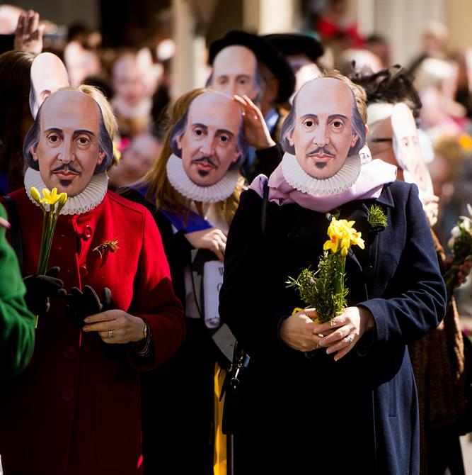 People wearing Shakespeare masks and carrying rosemary and daffodils in the parade