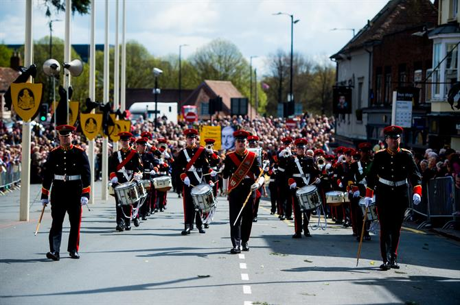 A marching band wearing black and red in the parade
