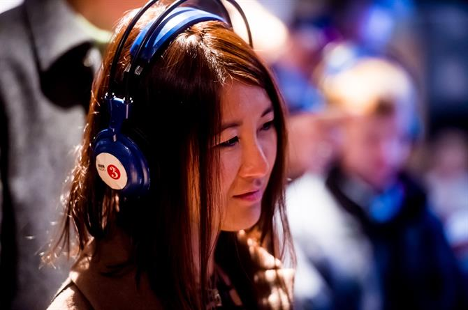 A long-haired woman wearing a pair of blue BBC Radio 3 headphones