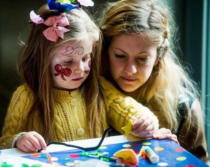 A child with her face painted doing arts and crafts with her mother, who watches closely