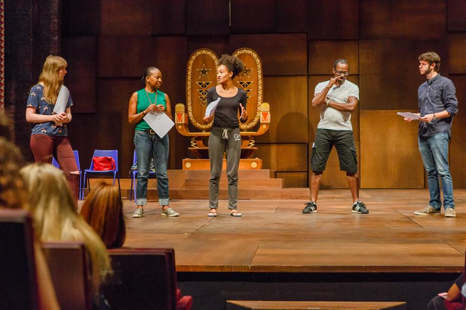 Four actors and an assistant director on stage, discussing Hamlet.