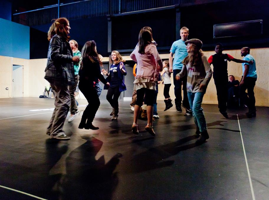 A group of children jump in the air in a Summer Skills workshop.