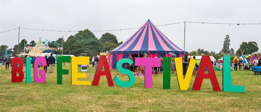 Large letters spelling out Big Feastival in front of a stripy marquee