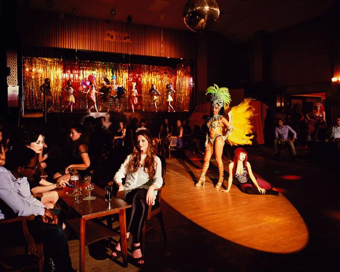 A colour photograph showing a dance floor with two performers in a spotlight, people sitting at tables in the foreground and a row of performers on a glittering stage in the background.