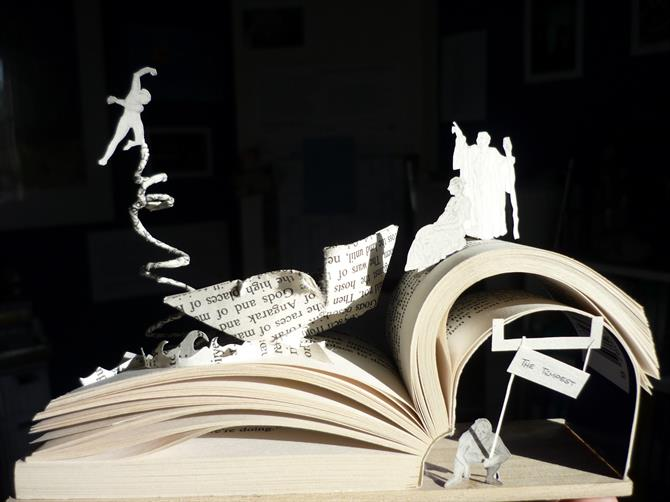 Book held open with paper sculpture rising from within it, featuring a boat and three figures. Underneath the book is a character crouching under the title 'The Tempest'.