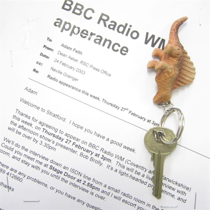 A collage featuring a memo for a radio appearance and a key on a dinosaur key ring.