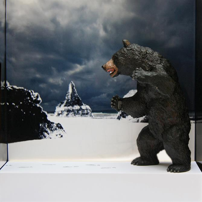 A plastic grizzly bear standing in a landscape featuring snow and rocks and a photographic backdrop of the sky.