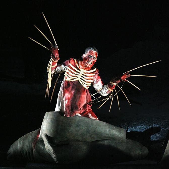 Julian Bleach as Ariel, The Tempest, 2006, in a blood-stained white gown wearing skeletal wings and breastplate, emerging from the body of a seal.