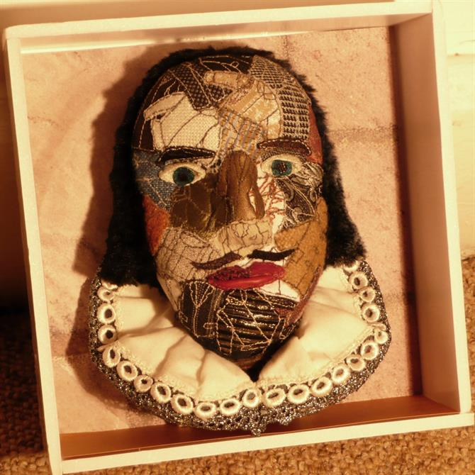 A representation of Shakespeare's head, including a gold trimmed ruff, and sewn together in a patchwork of rich materials.