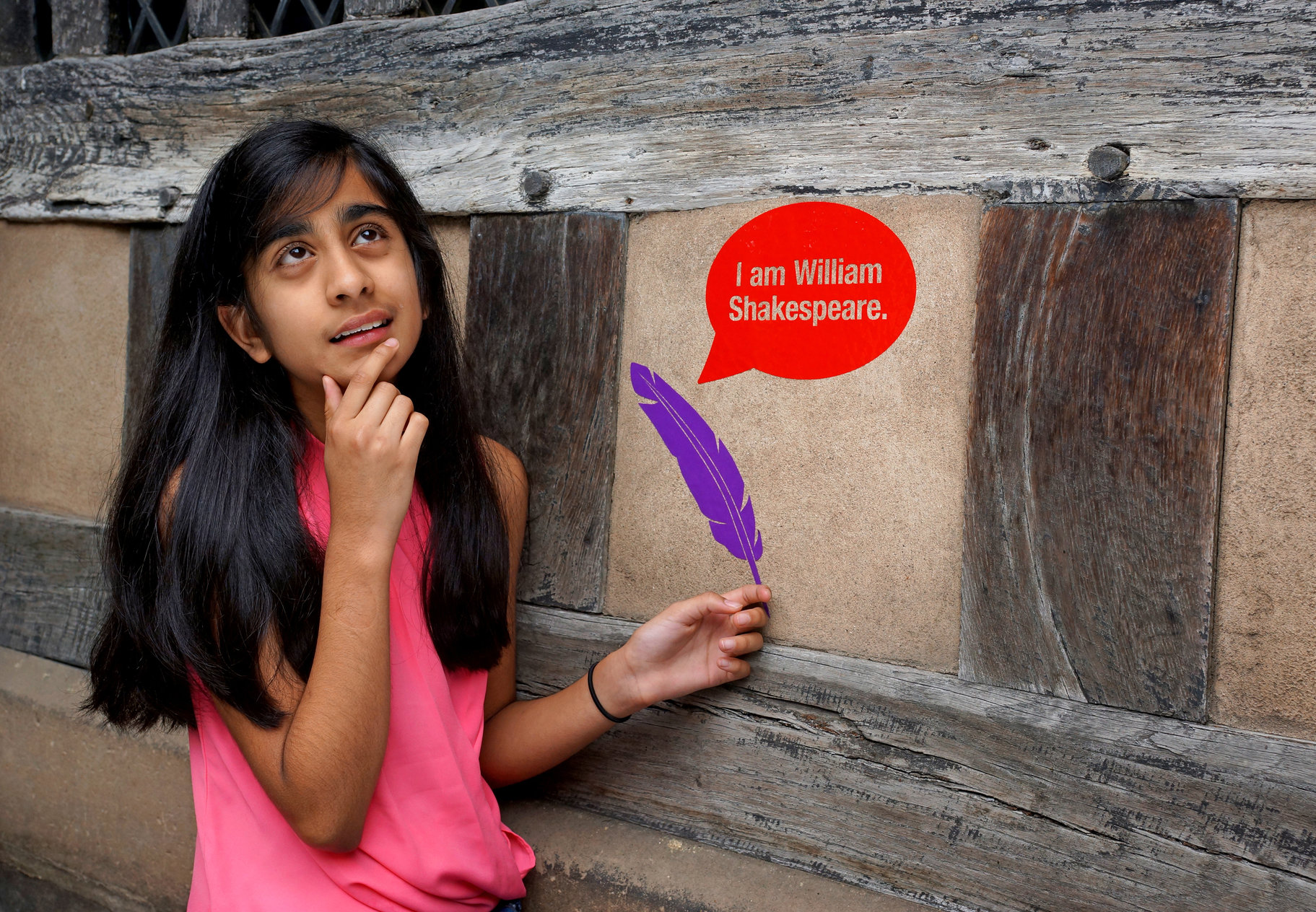 A girl standing in front of a historic wall, on which are a purple quill and a red speech bubble reading 'I am William Shakespeare'.