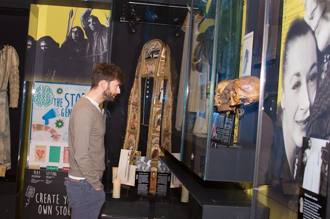 David Tennant looking at an exhibition of previous costumes and props from past shows, including multiple skulls used in Hamlet