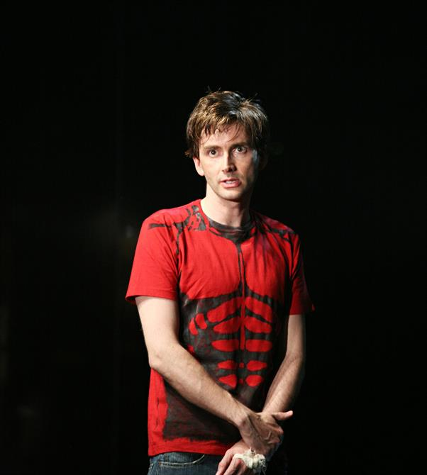 David Tennantin blue jeans and a red T-shirt depicting a skeleton, hands crossed in front of him
