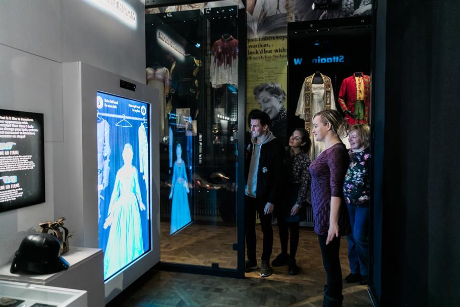 A group gathered around a woman who is standing in front of a digital mirror. The mirror shows her wearing a digital costume
