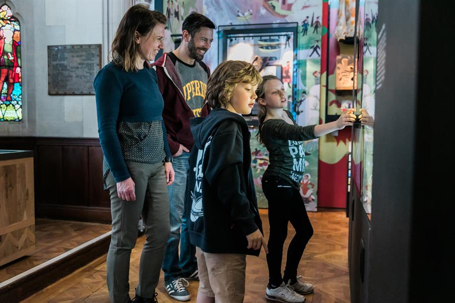 A mother and father with a boy and a girl looking at an item in an exhibition