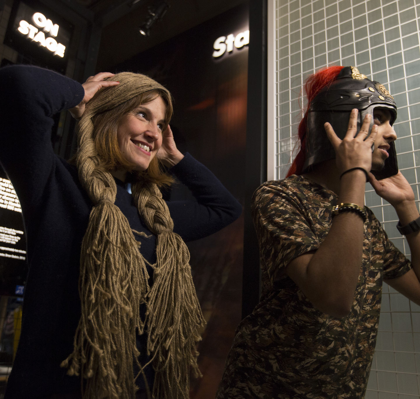 A woman trying on long plaited hair and a man trying on a metal helmet