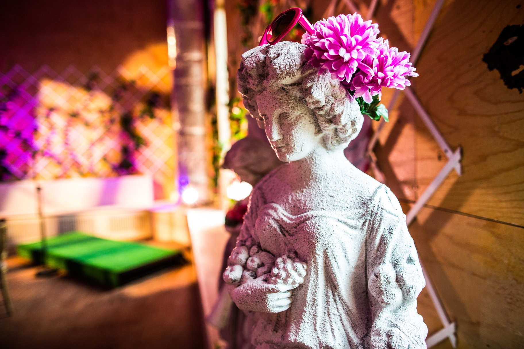 A stone statue in the middle of the room with pink flowers and sunglasses on her head.