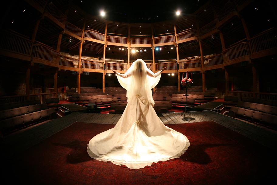 A woman in a wedding dress and veil stand on the Royal Shakespeare Theatre stage, facing the auditorium