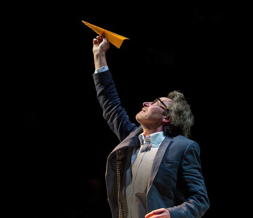 A man holds a yellow paper aeroplane above his head.