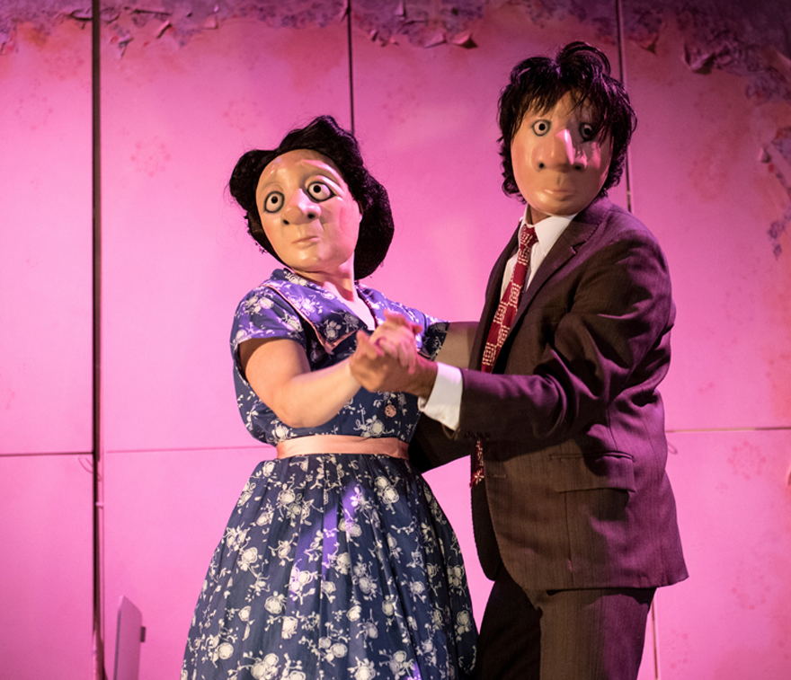 A man and woman dance wearing full face masks.