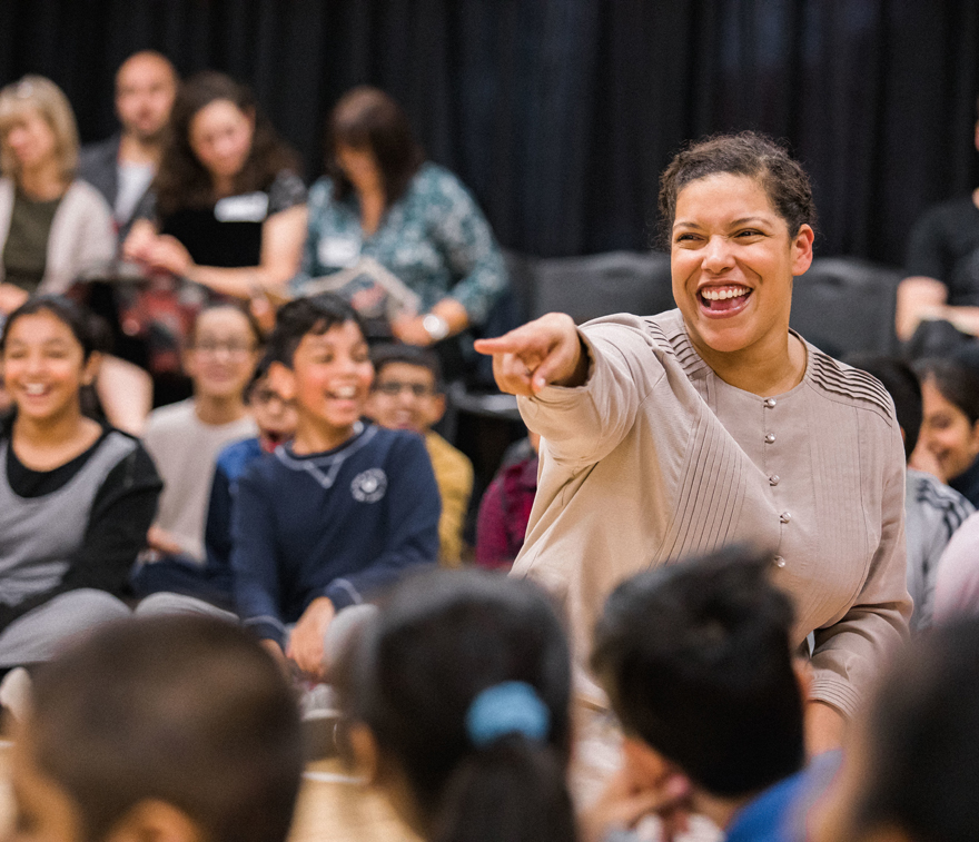 A smiling woman points a finger at a group of laughing school children.