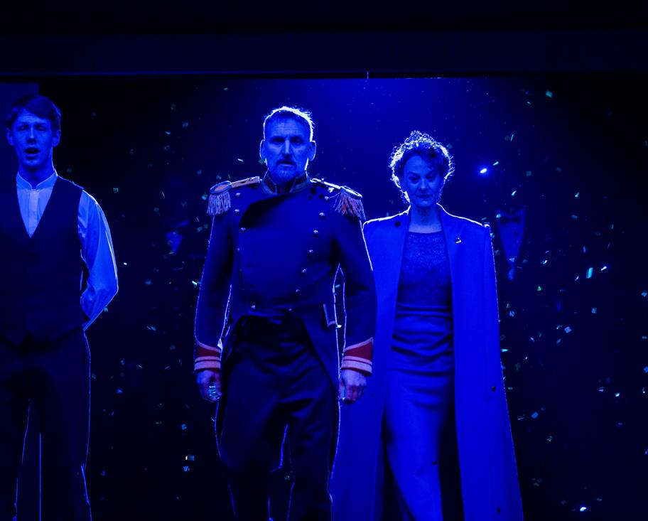 A king and queen walk together, bathed in bright blue light.