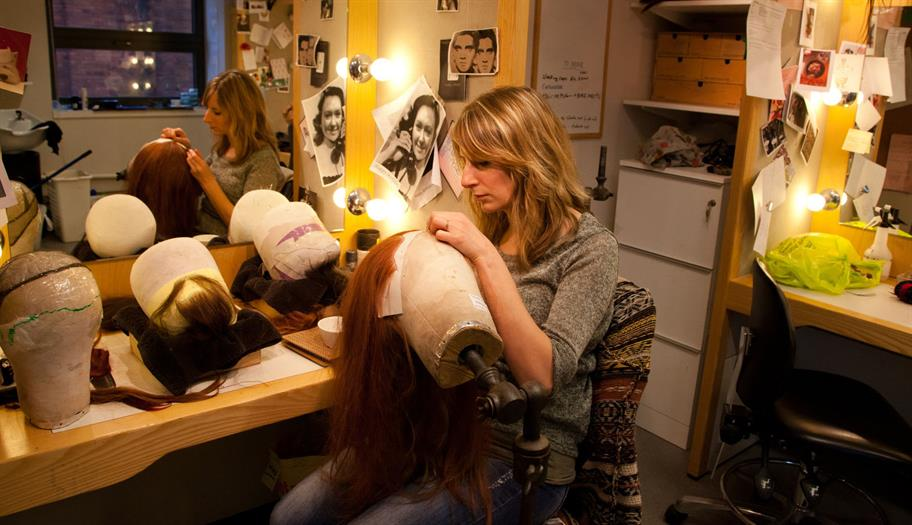 A blonde woman in a dressing room stitching a long red wig onto a model head