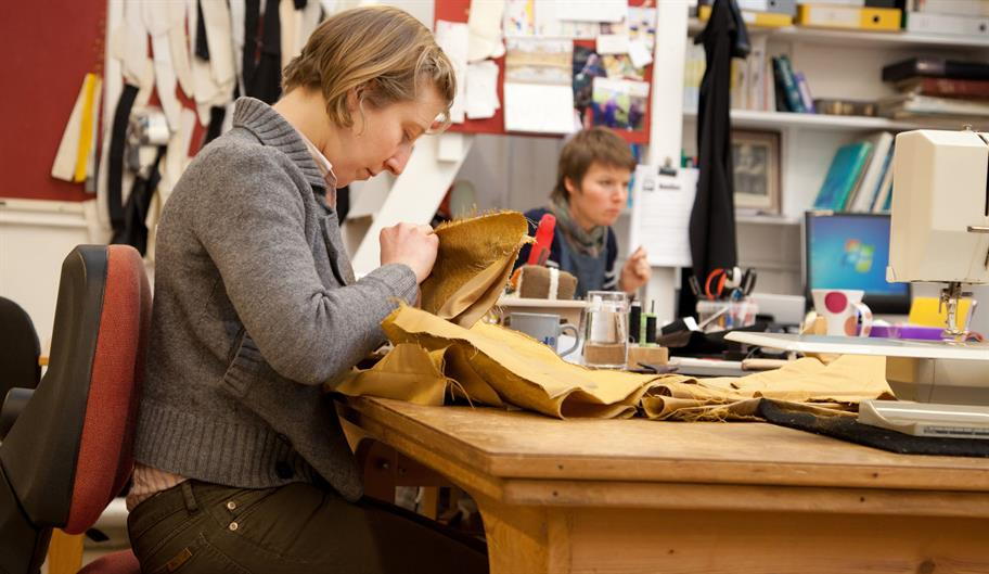 A costume maker sitting in an office, stitching on a piece of yellow cloth