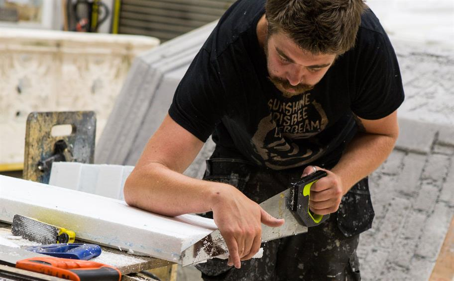 A man in a black t-shirt sawing off a white plank in a workshop
