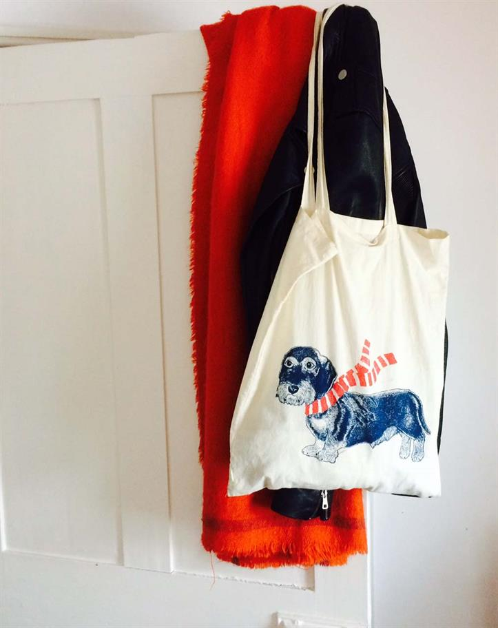 cream coloured cotton bag with a picture of a dog wearing a scarf, hanging on a white bedroom door