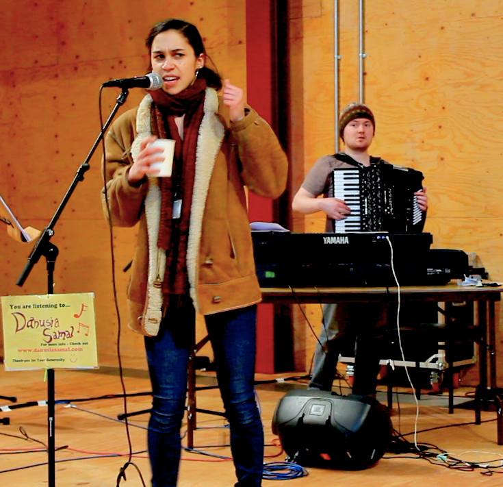 Danusia in scarf and sheepskin coat with clenched fist and a polystyrene cup looking angry, a man plays accordion in the background