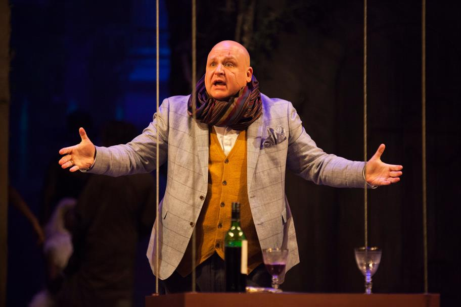 Byron Mondahl as Philario in Cymbeline, wearing a grey suit, yellow waistcoat and a rich scarf