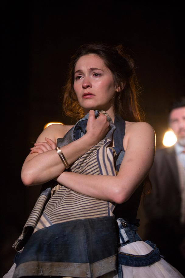 Bethan Cullinane as Innogen, with a metal bracelet on her arm and hugging a blue striped jacket to her chest